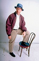 Man, 40-45, smiling at camera with foot on chair