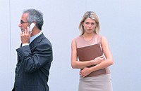 Businessman talking on cell phone, businesswoman looking at camera