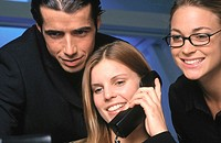Businesswoman talking on phone, two businesspeople in the background looking interested