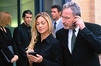 Businessman talking on cell phone, businesswoman with organizer, three businesspeople in the background