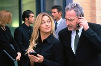Businessman talking on cell phone, businesswoman with organizer (thumbnail)