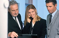 Three businesspeople looking on laptop, businesswoman talking on phone