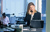 Businesswoman talking on phone, working with laptop