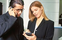 Businesswoman working with personal organizer, businessman talking on cell phone