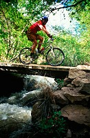 Mountain biker rides over a small bridge
