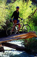 Mountain biker standing over a river