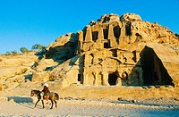 Graves carved in the rock and Bedouin rider at fore, archeological site of Petra. Jordan