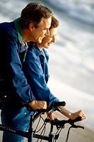 Mature couple holding bicycles on the beach