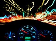Car dashboard and streaks of colourful neon lights