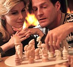 Couple playing chess in front of fireplace