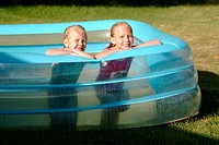 Girls ages play in an inflatable kiddie pool in front yard