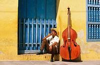 Bass player sat in a doorway with his Double bass. Trinidad de Cuba. Cuba