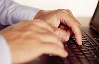 Man using a laptop - closeup of hands on keyboard