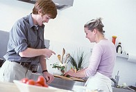 Young couple in kitchen (woman chopping herbs)