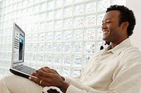Black man, in profile, holding computer (thumbnail)