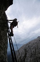 Outline of a climber on an iron ladder with cloudy sky in the background, Piscadue climbing trail, Dolomites, Sella, Italy