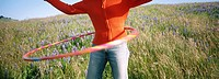 Woman and hula-hoop in field of flowers. Northern California