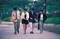 Four young executives walking outdoors, Malaysia