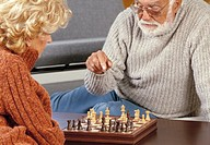 elderlyl couple playing chess