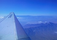 Plane wing during flight over mountains
