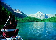 USA, man paddling boat in mountainous region