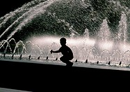Silhouette of boy crouching on edge of fountain
