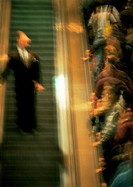 Crowd of people going up an escalator, one man coming down, blurred
