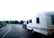 Car with mobile home driving on road, blurry (thumbnail)