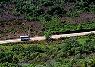 Bus traveling on mountainside road, blurry