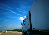 Semi-truck on highway, partial view, road and blue sky in background