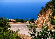 France, Corsica, road curving around mountain, sea in background