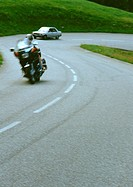 Motorcycle and car on winding road, blurred