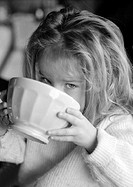 Little girl drinking from bowl, b&w