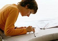 Woman bending over table, holding set square and pen, side view