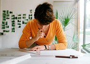 Woman bending over table, holding set square and pen (thumbnail)