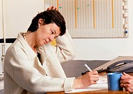 Woman sitting at desk, writing