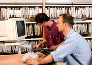 Man using computer, other man looking at files on shelves
