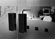 Desk behind glass doors, b&amp;w