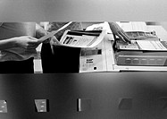 People using photocopier, mid section, b&amp;w