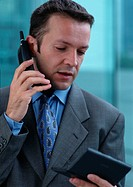 Man using cell phone while looking at pocket computer, portrait
