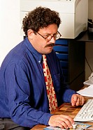 Man sitting at desk, holding mouse
