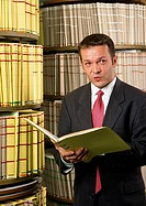 Man holding file, shelves in background