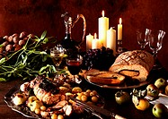 Dishes of meats, fruits and vegetables, with carafe of wine and candles in background