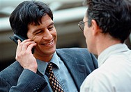 Two businessmen, one holding cell phone, smiling