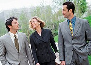 Three business people walking outside
