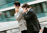 Two businessmen using cell phones outside, side view