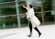 Businessman walking in street, hand raised, blurred