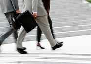 Business people walking, low section, blurred, b&w