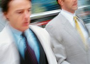 Two businessmen walking outside, close-up, blurred