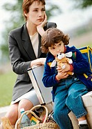 Businesswoman and child sitting, child hugging stuffed dog